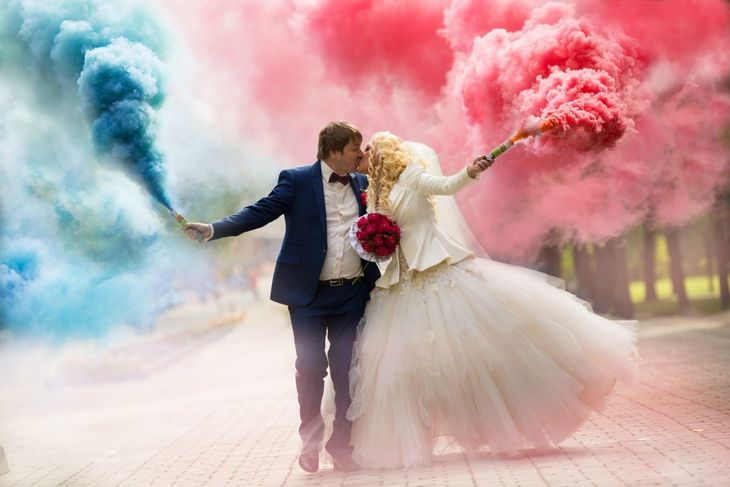 Жених и невеста с шашками цветного дыма